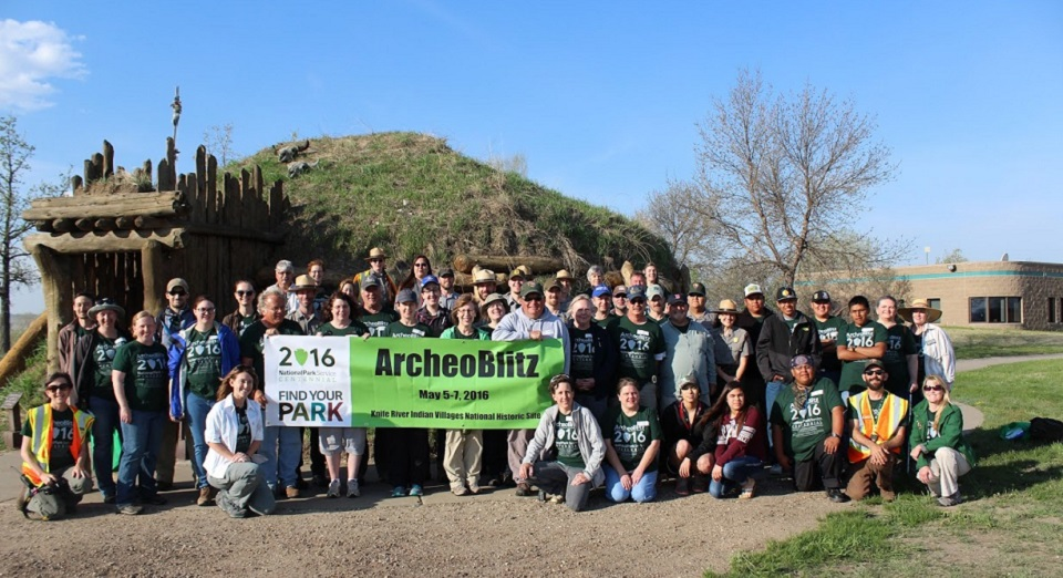 "Group of people standing in front of an earthlodge holding an ""Archaeoblitz"" sign"