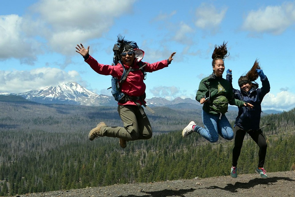 Three people jumping with mountains in background
