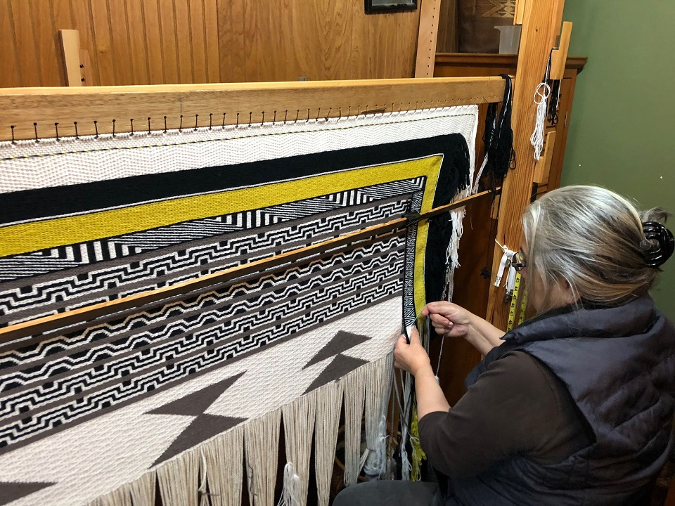 Woman weaving a Generations Robe