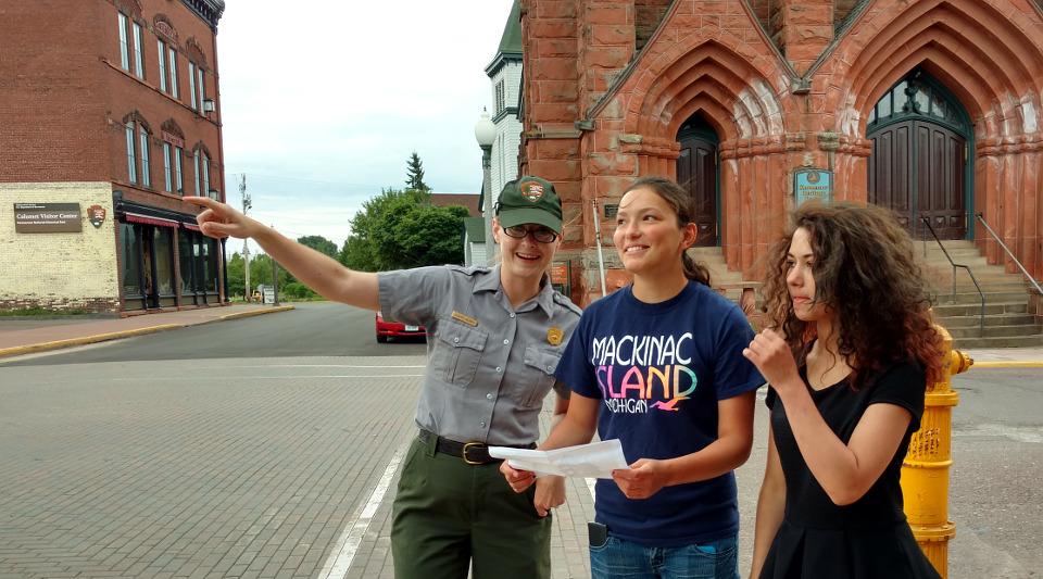 Park ranger pointing out historic buildings to two women