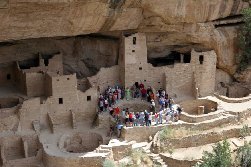 A crowd of visitors by ancient Pueblo ruins