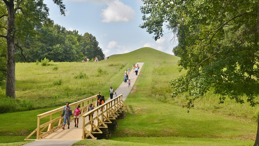 Families walking on a path down the side of a prehistoric earthen mound