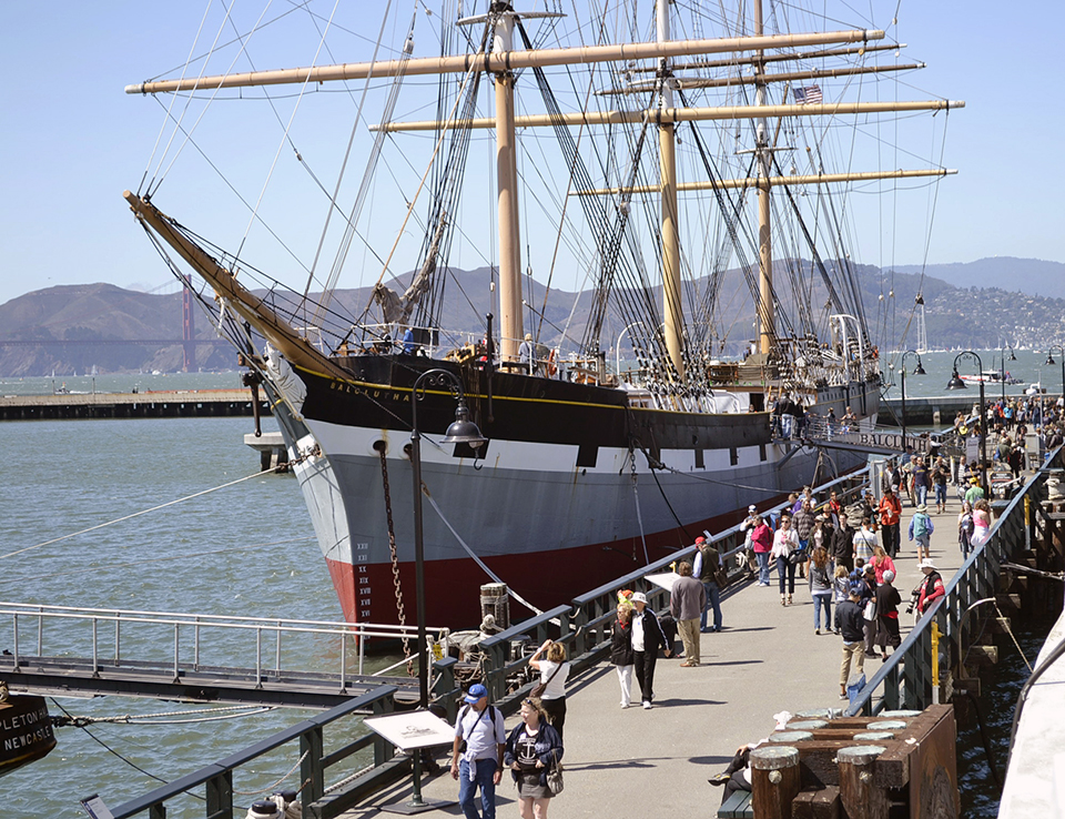 Crowd visiting a historic frigate docked at a pier