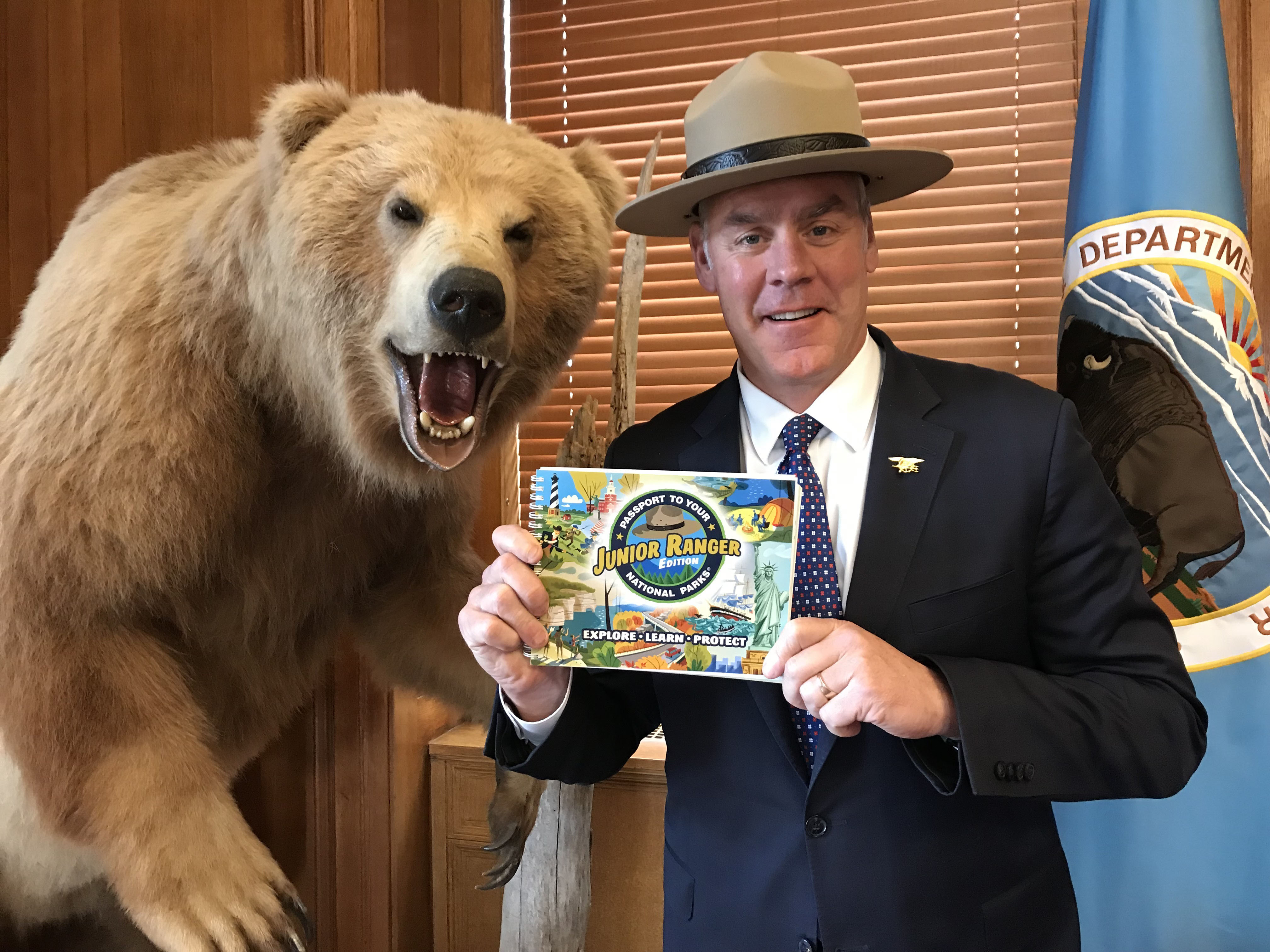 U.S. Secretary of the Interior, Ryan Zinke holding the new Junior Ranger Passport book while standing next to a stuffed bear.