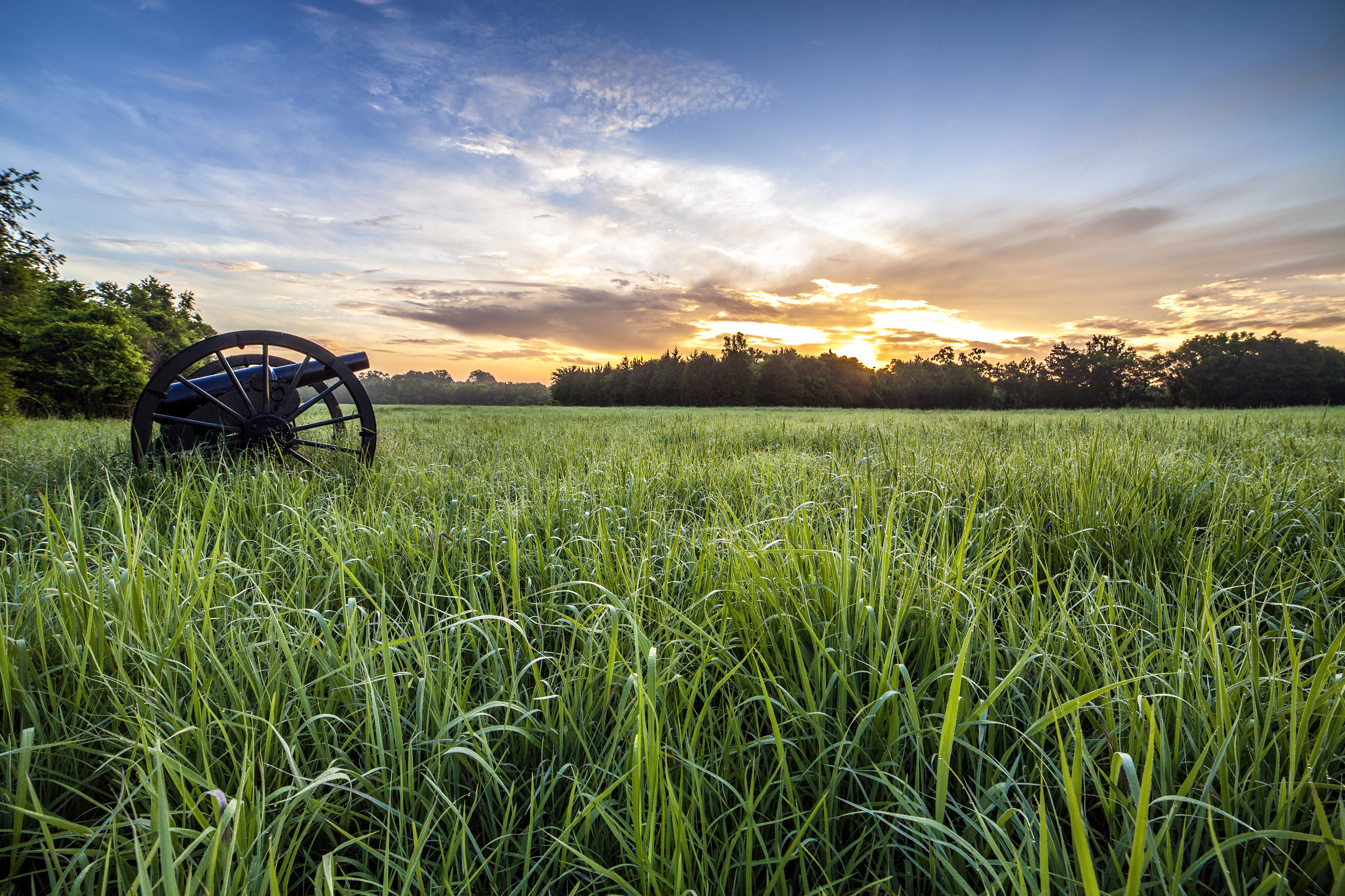 Civil war-era canon sits in a field of grass at sunset