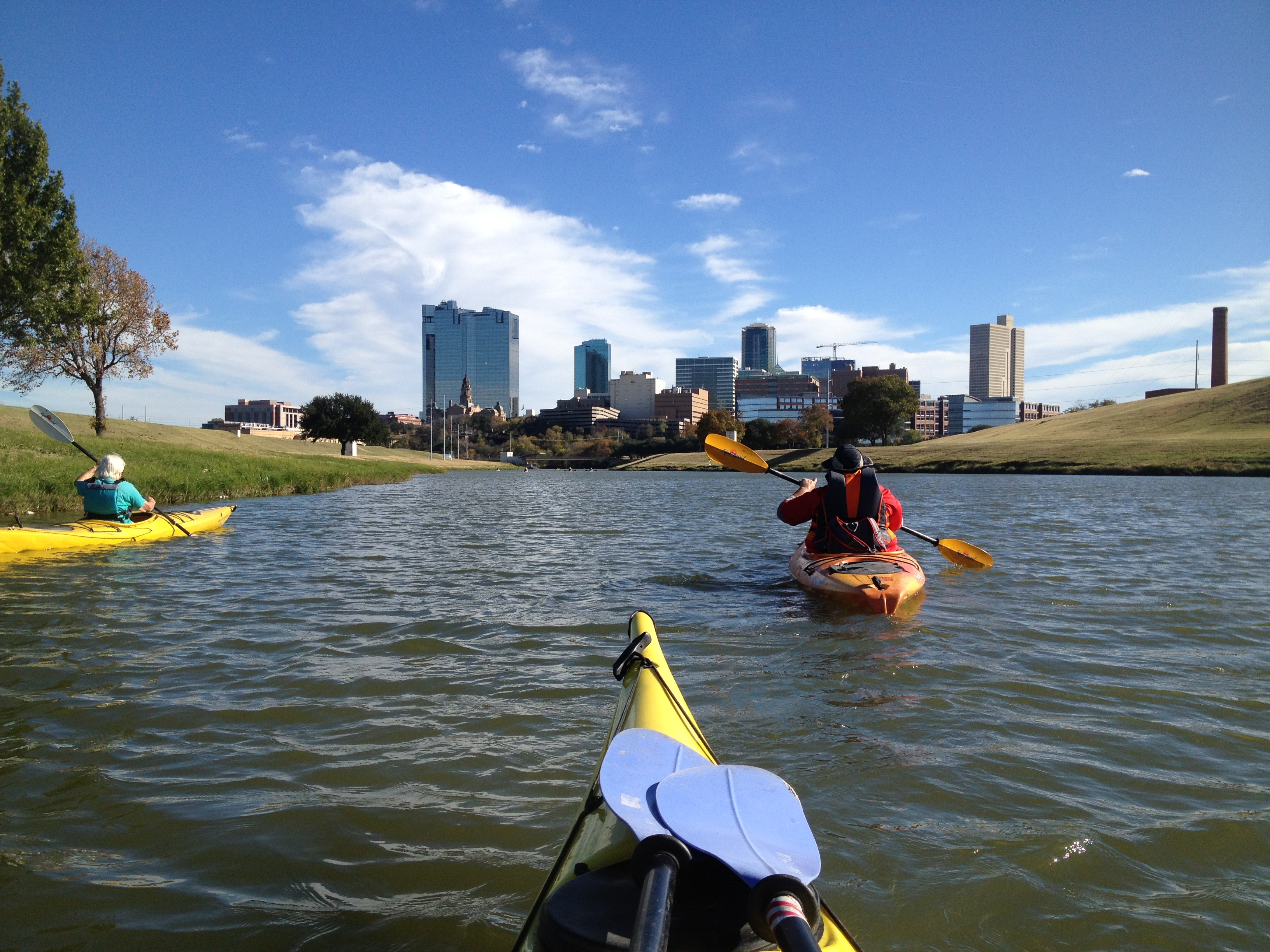 Three people kayaking on a river lined with grass and dotted by a couple of trees on a sunny day, a city with tall buildings in the distance.