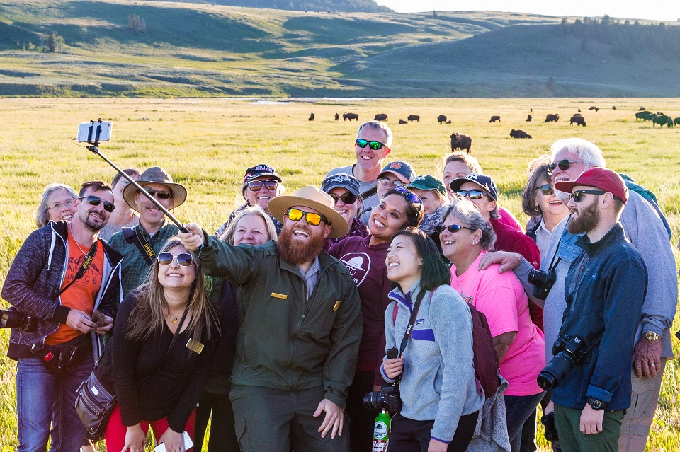 Ranger taking a selfie with a tour group with bison herd in the background