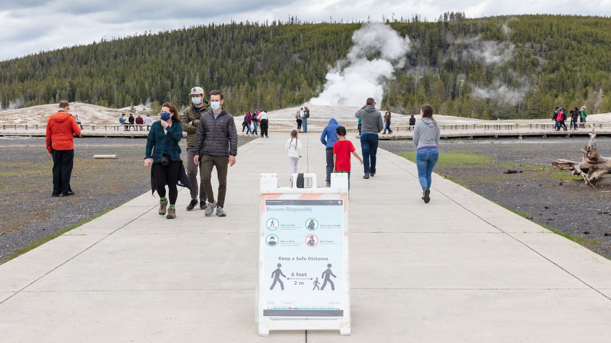 "Visitors wearing face masks use a walkway that leads to a steaming geyser in the background. The groups of visitors are physically distant. In the foreground is a sign propped on the ground that reads ""Recreate Responsibly. Stay on the trail."""