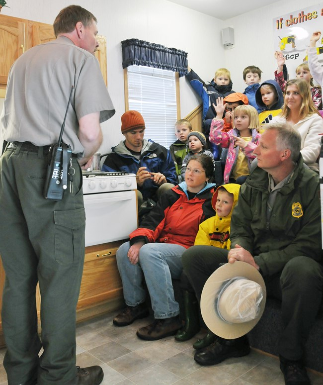 Park ranger talks to a group of children and adults about fire prevention