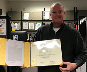 Hal Spencer holds a Superior Service Award