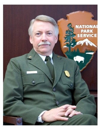 Director Jarvis sits posed in his park service uniform.