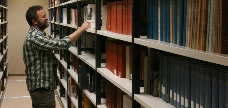 A man pulls a book from a shelf