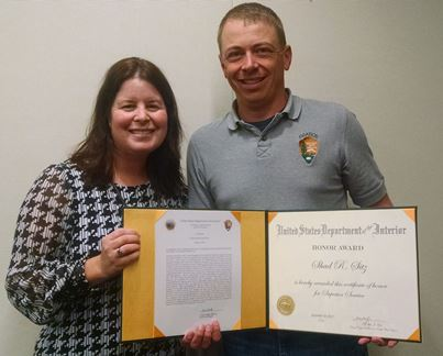 Acting Regional Director Stephanie Burkhart (left) and Shad Sitz (right) hold folder with Superior Service Award.