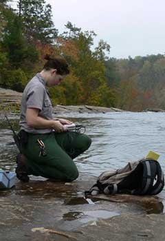 A woman in a National Park Service uniform kneels on a rock by a river entering data into a hand-held device. The trees that line the river are beginning to turn orange and yellow.
