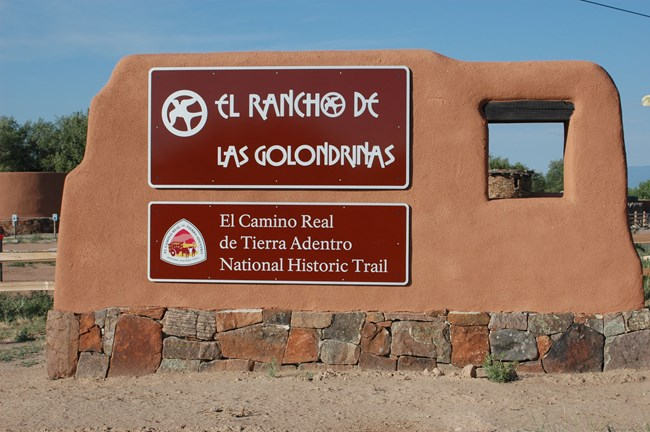 A large brown sign at the entrance to el Golondrinas, wrapped in adobe.