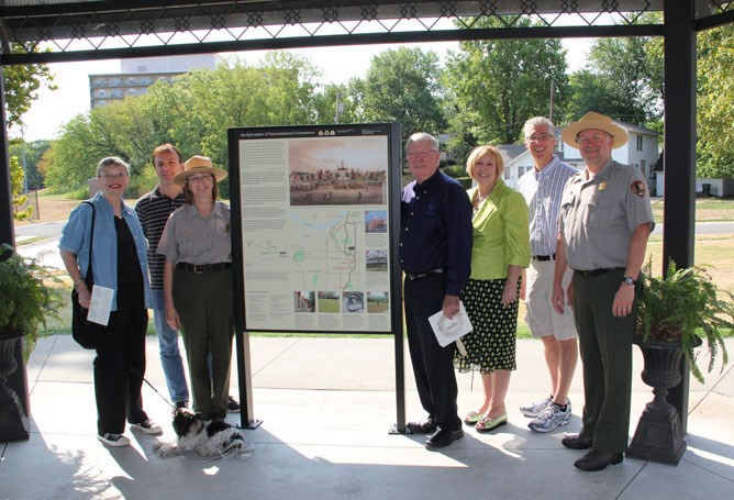 Seven people stand in front of a tall exhibit showing images and a map, surrounded by trees.