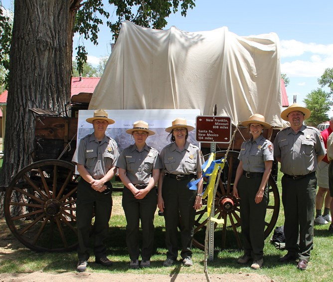 Five rangers in front of a Prairie Schooner wagon