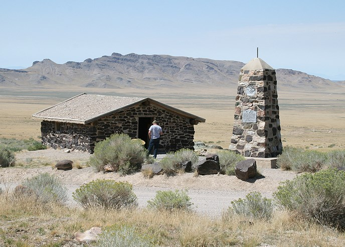 Person in front of a Pony Express station building that is made out of stone with a wood roof.