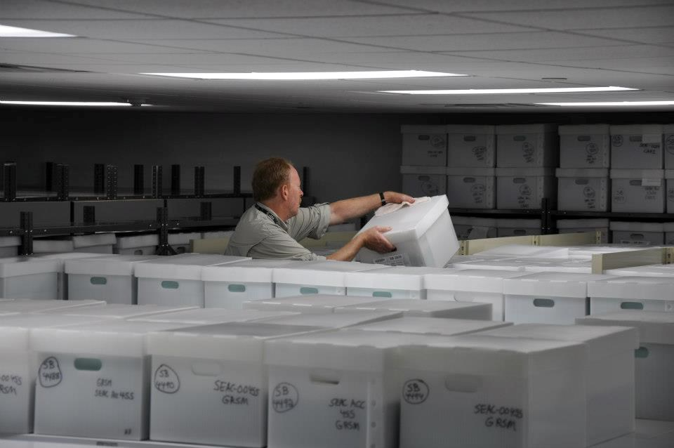 Museum Specialist Hank Kratt organizes boxes in the ACIM storage