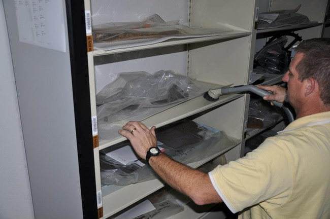 Museum Technician Charlie Sproul cleans shelves in ACIM storage