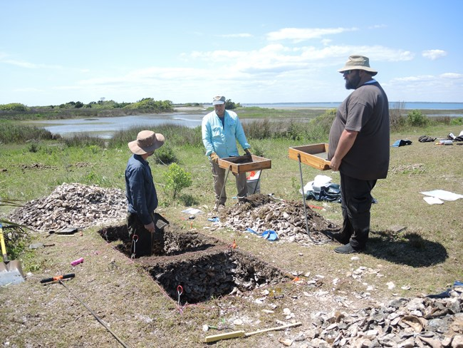 SEAC archeologists excavating at a shell midden site