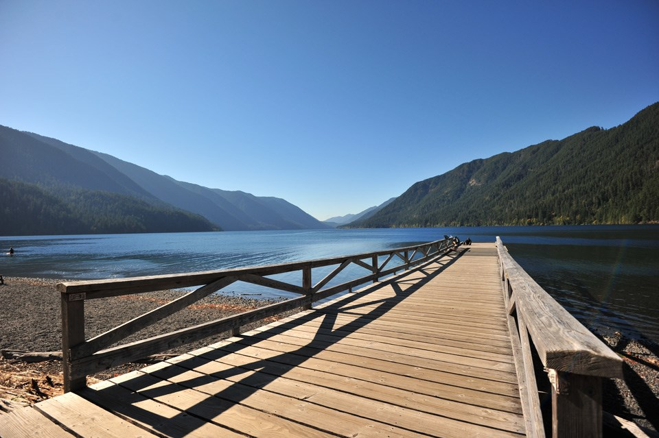 Long wooden dock extends into bright blue water at Lake Crescent Lodge