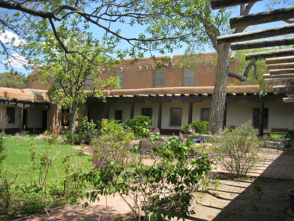 Old Santa Fe Trail Building landscape with adobe building, patio, and courtyard.