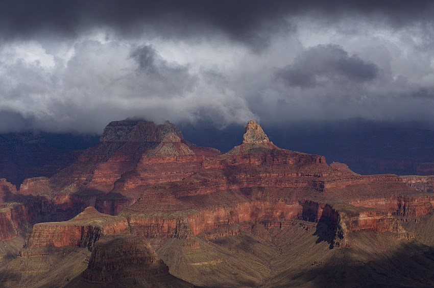 Dark storm clouds hang above inner canyon cliffs in Grand Canyon National Park.