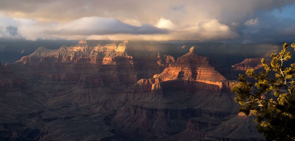 Sunlight shines through clouds above the Grand Canyon. NPS photo.