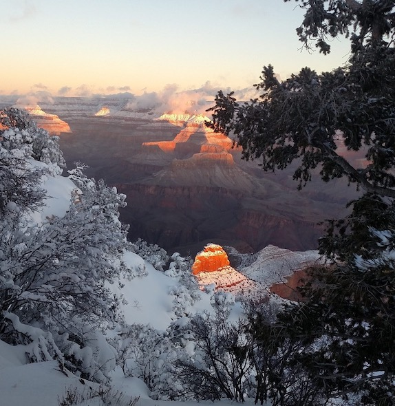 Snow brightens the rim of the Grand Canyon, and sunlight shines on O'Neil Butte in the inner canyon.