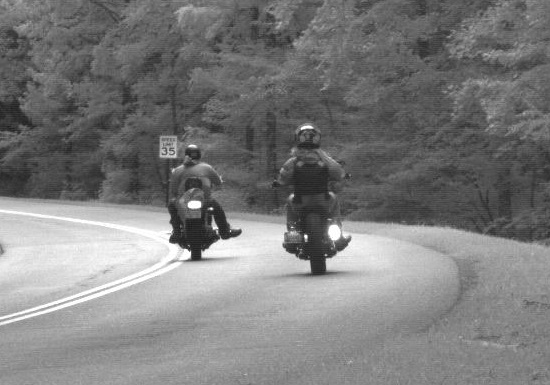 Two motorcyclists travel along a forested roadway in Great Smoky Mountains National Park.