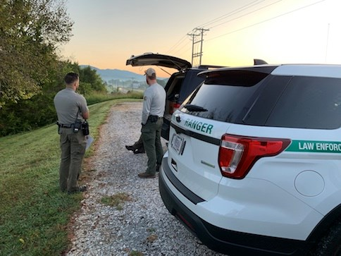 A US Park Ranger, Special Agent, and another officer have an early morning conversation near their vehicles. NPS photo.