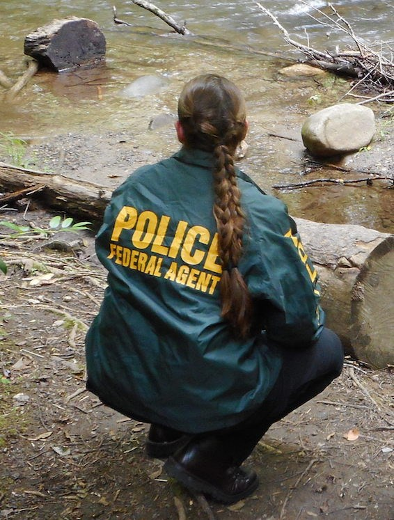 "An ISB Special Agent crouches near a stream bank. She wears a green jacket with the words ""Police"" and ""Federal Agent"" printed across the back."