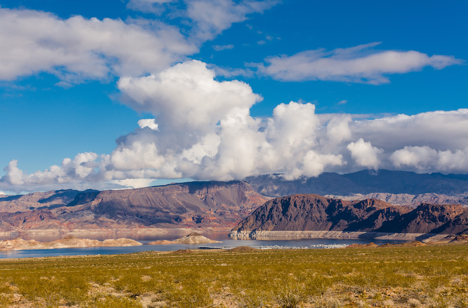 White clouds hang in a blue sky above Boulder Basin in Lake Mead National Recreation Area, with a desert landscape in the foreground and the lake and marinas in the distance. NPS photo by A Cattoir.