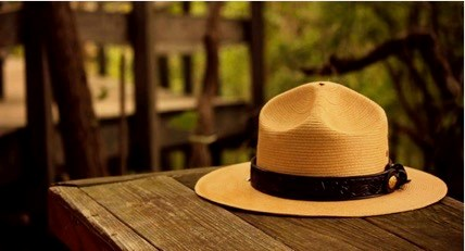"The iconic ""flat hat"" of a US Park Ranger rests atop a wooden table."