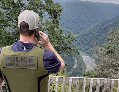 A Special Agent with the NPS Investigative Services Branch speaks on a mobile phone while overlooking a river.