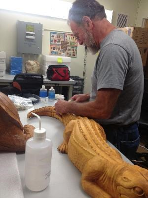 Conservator Al Levitan treating the John Segeren carvings from Everglades National Park Flamingo Museum