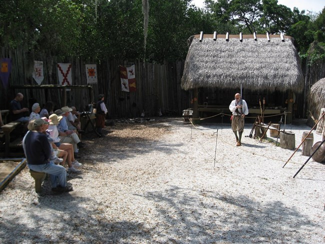 Costumed interpreter demonstrating sixteenth-century European weaponry to De Soto National Memorial visitors at the park's reconstructed Camp Uzita