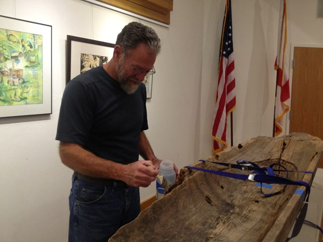 Conservator treating a Seminole canoe on exhibit at Big Cypress National Preserve