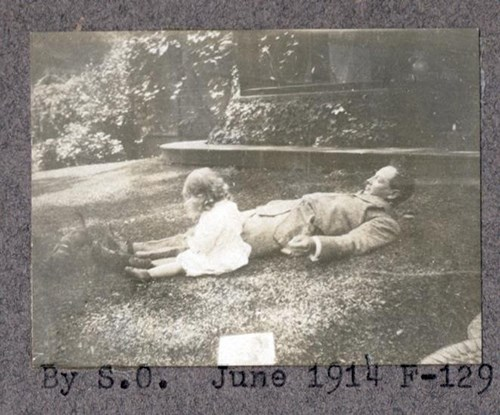 A child sits beside a man in suit who is laying on his back in the grass, 1914