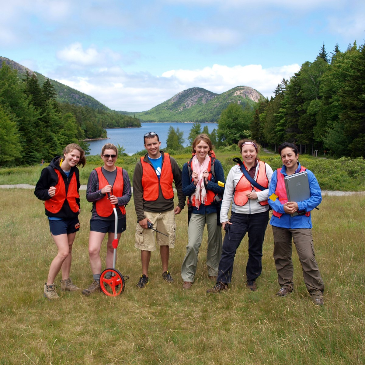 Interns during field trip to Acadia, posing in safety vests and work gear in front of Jordan Pond.