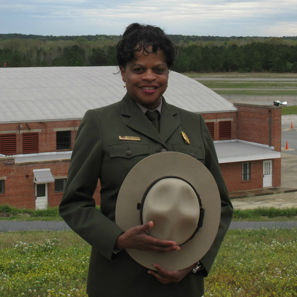 A woman in an NPS uniform faces the camera