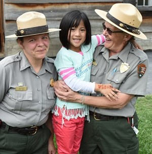 Two rangers smile with a young girl during an event.