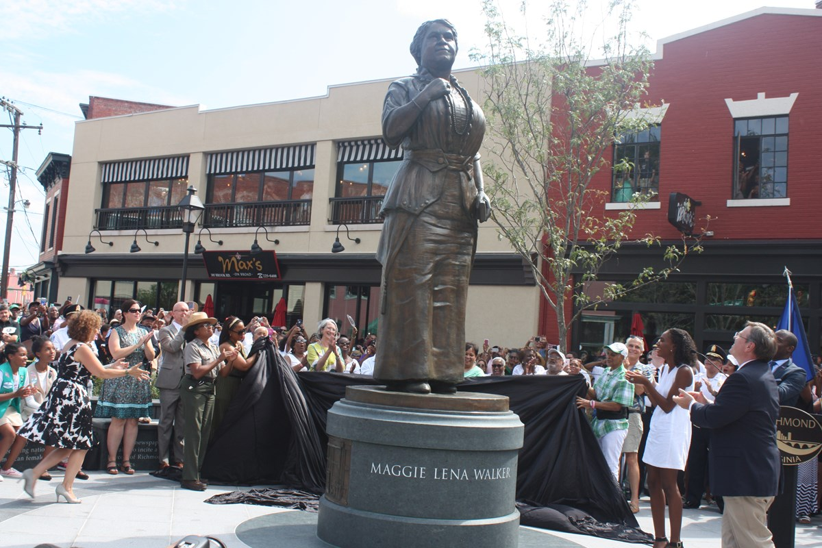 Crowd gathers around a new statue of Maggie Walker in downtown Richmond, VA