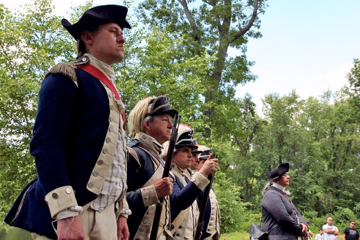 Men in 18th century garb stand in formation for an event.