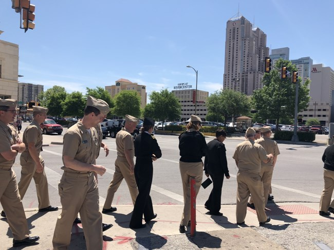 A group of men and women in tan uniforms walk along a street.