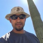 A man in sunglasses stands in front of a saguaro