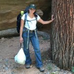A woman in green ball cap and hiking backpack stands with hand on a tree.