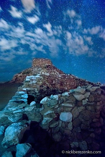 Stone walls with bluish tint and starry sky and clouds above