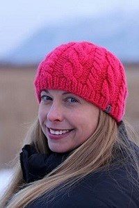 a woman in a pink winter hat smiles